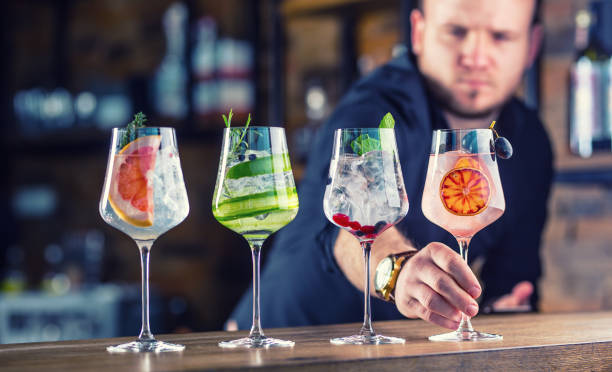 Barman in pub or restaurant  preparing a gin tonic cocktail drinks in wine glasses.